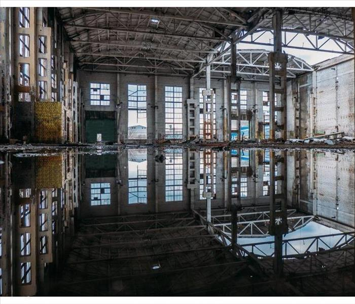 Inside of flooded dirty abandoned ruined industrial building with water reflection of interior.